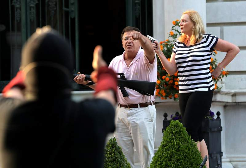FILE - In this June 28, 2020 file photo, armed homeowners Mark and Patricia McCloskey, standing in front their house along Portland Place confront protesters marching to St. Louis Mayor Lyda Krewson's house in the Central West End of St. Louis. Sen. Josh Hawley on Thursday, July 16, 2020, urged Attorney General William Barr to launch a federal civil rights investigation of St. Louis' elected prosecutor, accusing Circuit Attorney Kim Gardner of abusing her power in her investigation of the McCloskey's who wielded guns while defending their home during a protest. (Laurie Skrivan/St. Louis Post-Dispatch via AP File)
