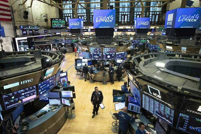 FILE - In this Friday, March 13, 2020, file photo, a trader walks on the floor of the New York Stock Exchange during President Donald Trump's televised speech from the White House, in New York. Stock markets are set for another week of turbulent trading as U.S. index futures fell sharply after the Federal Reserve slashed interest rates and more companies and governments took action over the weekend to shut down European and American society. (AP Photo/Mark Lennihan, File)