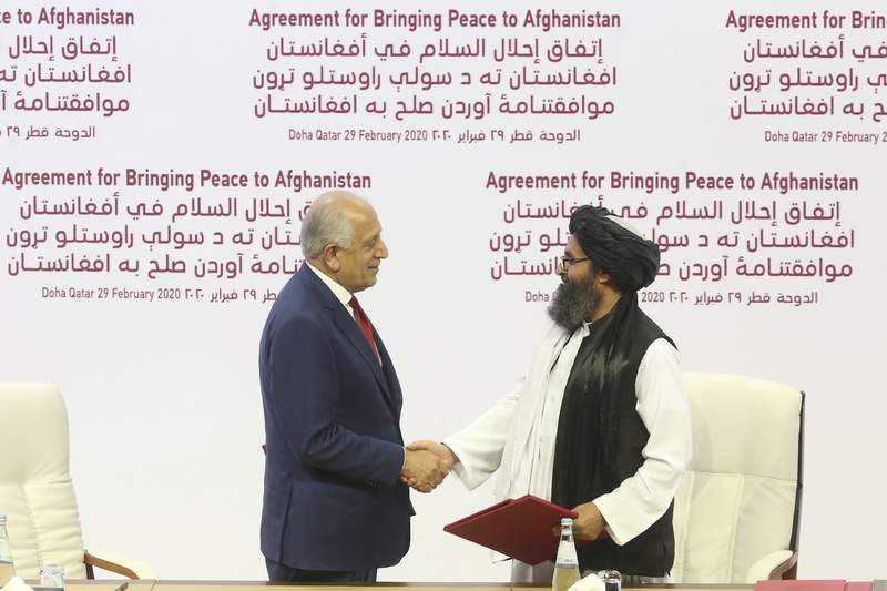 FILE - In this Feb. 29, 2020 file photo, U.S. peace envoy Zalmay Khalilzad, left, and Mullah Abdul Ghani Baradar, the Taliban group's top political leader shake hands after signing a peace agreement between Taliban and U.S. officials in Doha, Qatar. An Afghan official said Thursday, May 14, 2020, that a suicide attack in eastern Afghanistan targeted a military compound but was detonated before it reached the compound killing several civilians and wounding tens of others. The Taliban took responsibility for the bombing calling it retaliation for statements Tuesday by President Ashraf Ghani blaming Taliban for a brutal attack on a maternity hospital that killed tens of people, an attack that the Taliban were quick to condemn. (AP Photo/Hussein Sayed, File)