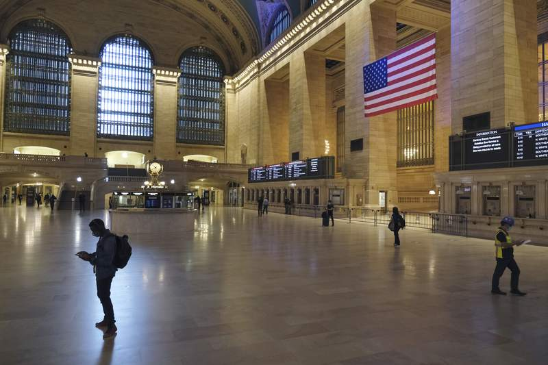 Commuter traffic is light during rush hour in Grand Central Station in New York, Monday, June 8, 2020. After months of a coronavirus crisis followed by protests and unrest, New York City is trying to turn a page when a limited range of industries reopen Monday. (AP Photo/Seth Wenig)