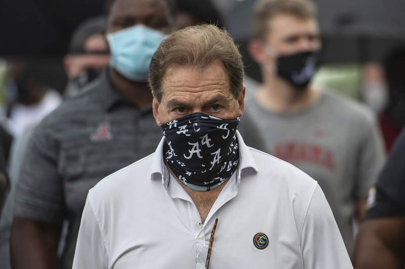 FILE - In this Aug. 31, 2020, file photo, Alabama head football coach Nick Saban leads his team as they march on campus, supporting the Black Lives Matter movement, in Tuscaloosa, Ala. The mid-week news that Alabama coach Nick Saban tested positive for COVID-19 added a challenging backdrop for the seasons first Top 5 matchup. Saban figures to be communicating his marching orders and input from home while offensive coordinator Steve Sarkisian is manning the show within the football building. (AP Photo/Vasha Hunt, File)