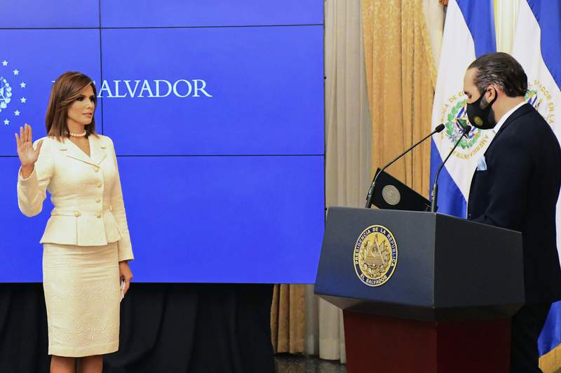 In this In this photo released by the El Salvador Presidential Press Office, Salvadoran President Nayib Bukele swears in Milena Mayorga as the country's next ambassador to the U.S., at Government House, in San Salvador, El Salvador, Thursday, Sept. 24, 2020.  A top 10 finalist in the 1996 Miss Universe pageant, Mayorga is a political neophyte with no previous diplomatic experience, having been elected to congress for the first time in 2018.(El Salvador Presidential Press Office via AP)