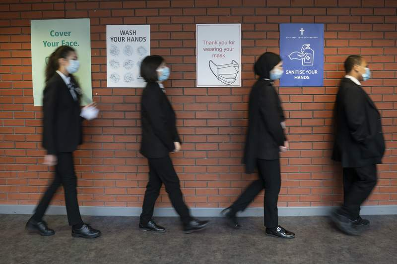 FILE  - In this Monday, March 8, 2021 file photo, pupils queue for a socially distanced assembly at a school in in Manchester, England. The independent body advising the British government on the rollout of coronavirus vaccines says the direct health benefits of offering the jabs to all healthy 12 to 15 year olds are marginal. With just two per million of healthy children needing intensive care treatment for COVID-19, the Joint Committee on Vaccination and Immunisation said the margin of benefit, based primarily on a health perspective, is considered too small to support advice on a universal program. (Jon Super/PA via AP, File)