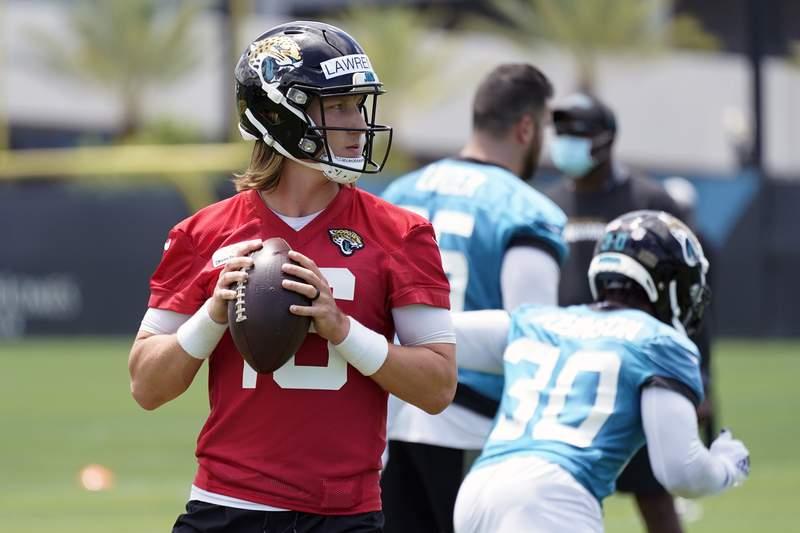Jacksonville Jaguars quarterback Trevor Lawrence looks for a receiver during an NFL football team practice, Tuesday, June 8, 2021, in Jacksonville, Fla. (AP Photo/John Raoux)