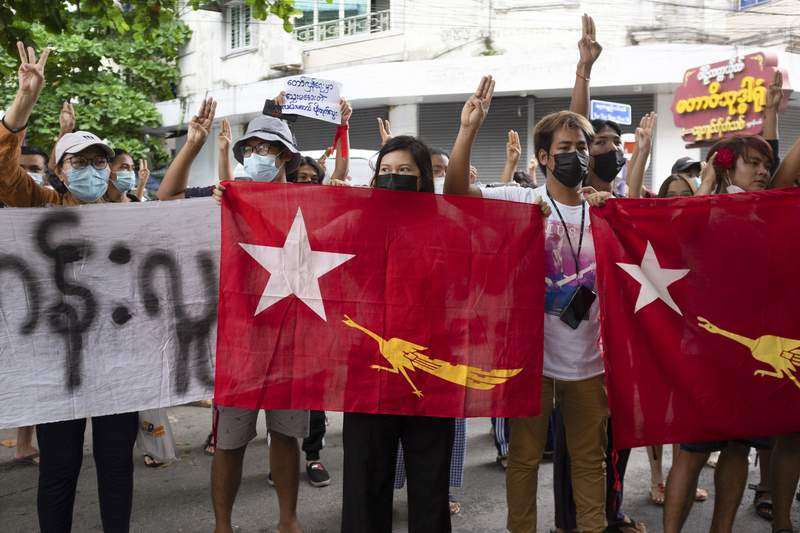 Protesters holding National League for Democracy (NLD) flags raise three-finger salutes during flash protests against the military coup at Bahan township in Yangon, Myanmar, Friday, June 25, 2021. (AP Photo)