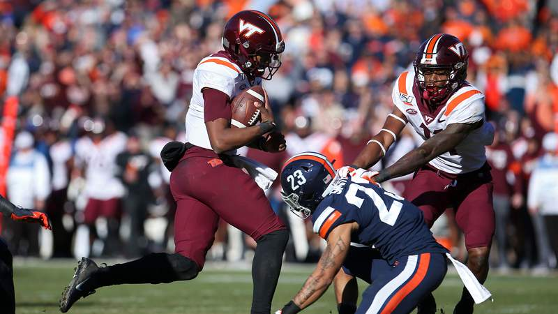 Hendon Hooker #2 of the Virginia Tech Hokies rushes past Heskin Smith #23 of the Virginia Cavaliers to score a touchdown in the second half during a game at Scott Stadium on November 29, 2019 in Charlottesville, Virginia. (Photo by Ryan M. Kelly/Getty Images)