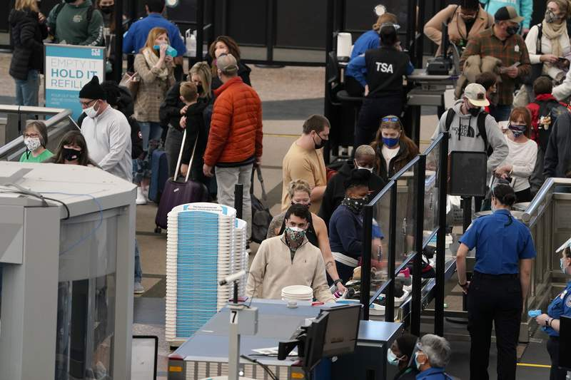 FILE - In this Thursday, Feb. 18, 2021, file photo, travelers wear face coverings as they queue up at the north security checkpoint in the main terminal of Denver International Airport, in Denver. Major U.S. airlines say they will ask passengers on flights to the United States for information that public health officials could use for COVID-19 contact tracing. The trade group Airlines for America said Friday, Feb. 19, that the carriers will turn over the information to the Centers for Disease Control and Prevention. (AP Photo/David Zalubowski, File)