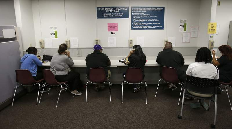 FILE - In this Sept. 20, 2013, file photo, visitors use the Unemployment Insurance phone bank at the California Employment Development Department office in Sacramento, Calif. Concerns are growing of possible fraud at California's unemployment agency after multiple reports of unsolicited debit cards arriving in people's mailboxes and a suspiciously high number of claims involving independent contractors, Thursday, Sept. 3, 2020. (AP Photo/Rich Pedroncelli, File)