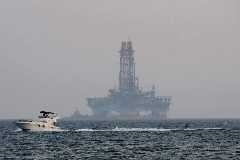 FILE - In this Sunday, July 5, 2020, file photo, an offshore drilling rig is seen in the waters off Cyprus' coastal city of Limassol as a boat passes with a skier. A climate change conference will underscore to policymakers in the Middle East and the east Mediterranean that the switch from fossil fuels to renewable energy sources is needed urgently because greenhouse gas emissions are helping to drive up regional temperatures faster than in many other inhabited parts of the world. (AP Photo/Petros Karadjias, File)