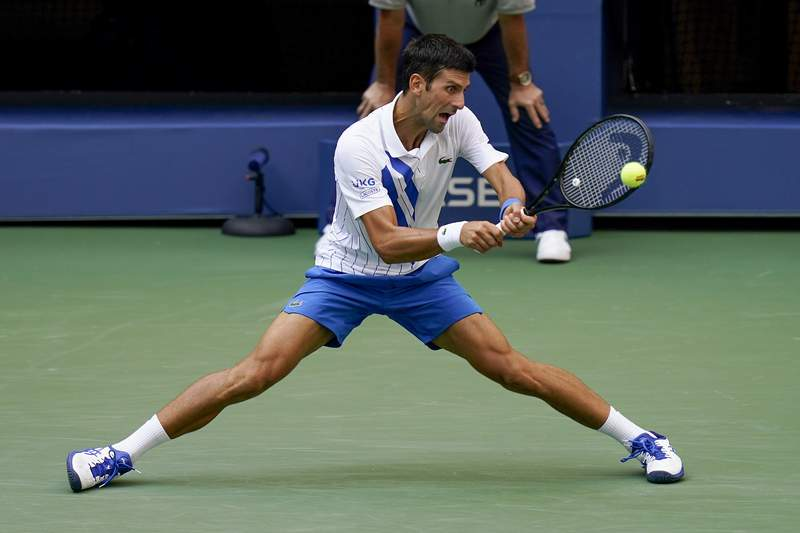 Novak Djokovic, of Serbia, returns a shot to Pablo Carreno Busta, of Spain, during the fourth round of the US Open tennis championships, Sunday, Sept. 6, 2020, in New York. (AP Photo/Seth Wenig)