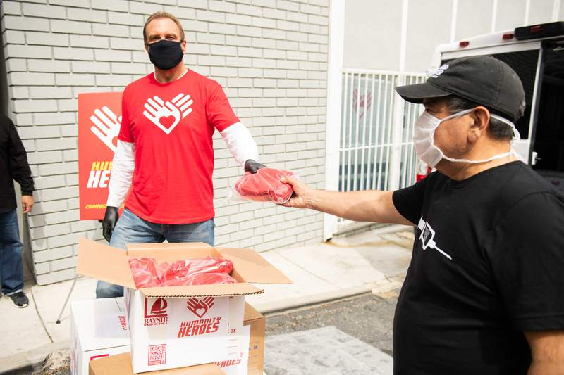 Michael Straumieitis hands out masks during the Humanity Heroes Los Angeles Face Mask Distribution on April 7, 2020.