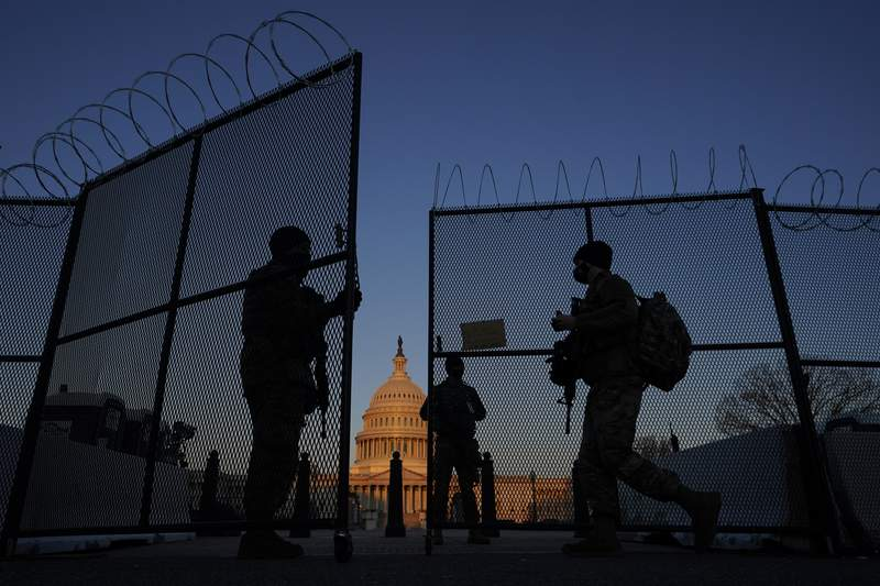 FILE - In this March 8, 2021, file photo, members of the National Guard open a gate in the razor wire topped perimeter fence around the Capitol at sunrise in Washington. Threats to members of Congress have more than doubled this year, according to the U.S. Capitol Police, and many members say they fear for their personal safety more than they did before the siege. (AP Photo/Carolyn Kaster, File)