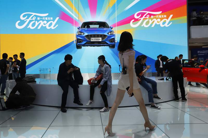 FILE - In this April 25, 2018, file photo, attendees visit the Ford booth during Auto China 2018 show held in Beijing, China.  Chinas government says it will postpone planned punitive tariffs on U.S.-made automobiles and other goods following an interim trade deal with Washington.  Sunday, Dec. 15, 2019s announcement came after Washington agreed to postpone a planned tariff hike on $160 billion of Chinese goods and to cut in half penalties that already were imposed. (AP Photo/Ng Han Guan, File)