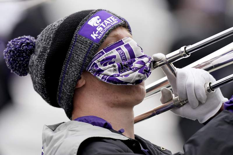 A member of the Kansas State marching band plays the trombone while wearing a face mask during the second half of an NCAA football game against Kansas Saturday, Oct. 24, 2020, in Manhattan, Kan.  (AP Photo/Charlie Riedel)