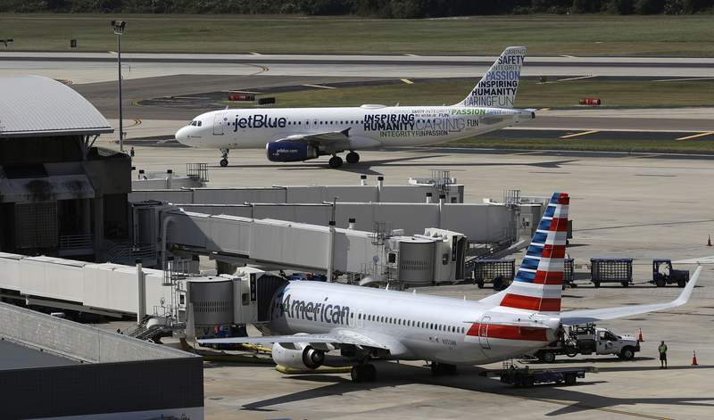FILE - A JetBlue Airbus A320 taxis to a gate Wednesday, Oct. 26, 2016, after landing as an American Airlines jet is seen parked at its gate at Tampa International Airport in Tampa, Fla. The Justice Department is suing to stop American Airlines and JetBlue from coordinating their flights in the Northeast. Government antitrust lawyers said Tuesday, Sept. 21, 2021, that the deal between the two airlines will reduce competition and lead to higher fares. (AP Photo/Chris O'Meara, File)