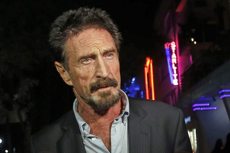 FILE  In this Dec. 12, 2012, file photo, anti-virus software founder John McAfee answers questions to reporters as he walks on Ocean Drive, in the South Beach area of Miami Beach, Fla. McAfee, the outlandish security software pioneer who tried to live life as a hedonistic outsider while running from a host of legal troubles, was found dead in his jail cell near Barcelona, Spain, on Wednesday, June 23, 2021. His death came just hours after a Spanish court announced that it had approved his extradition to the United States to face tax charges punishable by decades in prison, authorities said. (AP Photo/Alan Diaz, File)