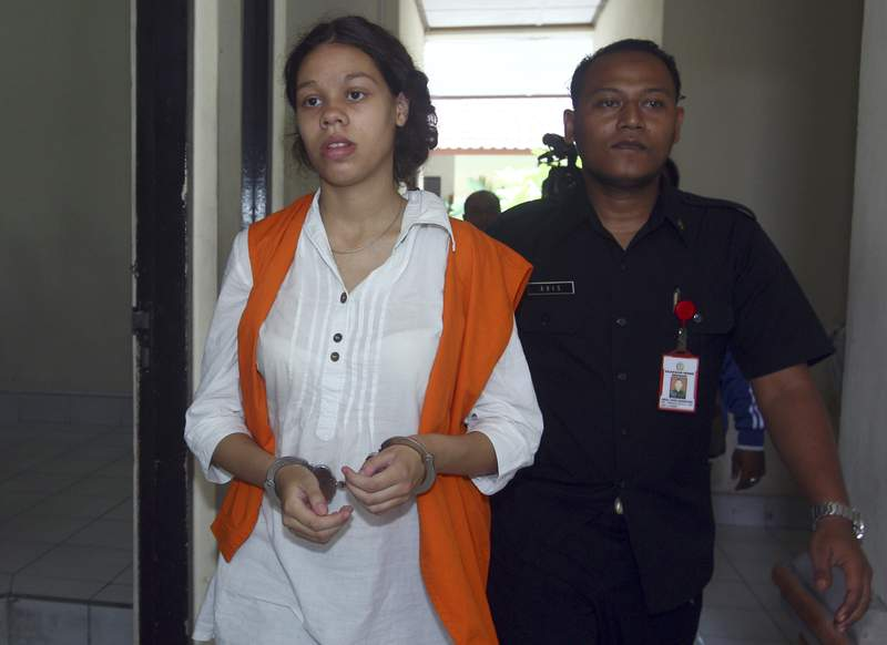 FILE - In this April 7, 2015 file photo, handcuffed Heather Mack of Chicago, Ill. is escorted by an Indonesian prison guard to a court room for her trial at Denpasar District Court in Bali, Indonesia. Mack, serving a 10-year sentence for assisting her then-boyfriend in her mother's murder and stuffing the body in a suitcase on Indonesia's tourist island of Bali in 2014 will be released from prison in October after completing her sentence, an Indonesian lawyer said Thursday, Aug. 26, 2021. (AP Photo/Firdia Lisnawati File)