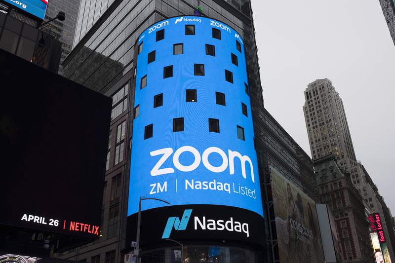 FILE - This April 18, 2019, file photo shows a sign for Zoom Video Communications ahead of the company's Nasdaq IPO in New York. Videoconferencing service Zoom is buying cloud contact center provider FiveTh9 in an all-stock deal valued at about $14.7 billion. Zoom Video Communications Inc. founder and CEO Eric Yuan said in a blog post that the acquisition will allow the company to accelerate its long-term growth by adding the $24 billion contact center market.  (AP Photo/Mark Lennihan, File)