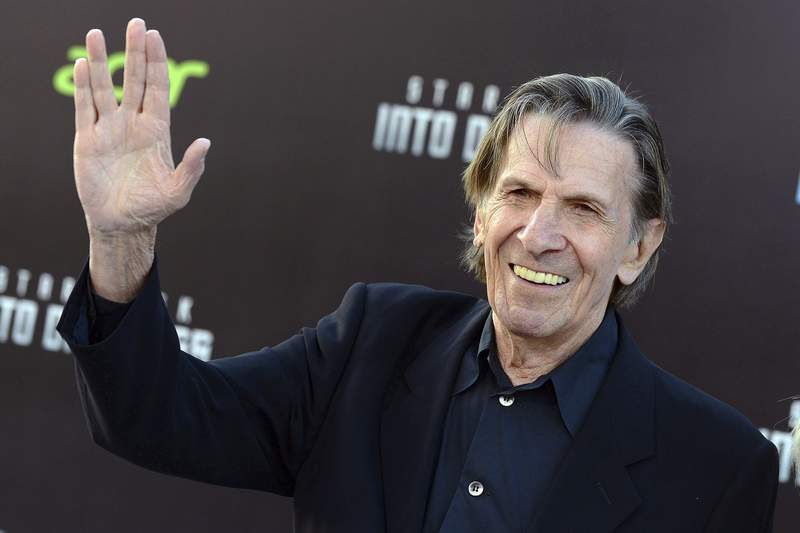 """FILE - In this May 14, 2013 file photo, Leonard Nimoy gives a """"Live Long and Prosper"""" hand gesture arrives at the LA premiere of """"Star Trek Into Darkness"""" in Los Angeles. The Museum of Science, Boston, in collaboration with the Nimoy's family announced the development of a monument shaped in the hand gesture made famous by the actor's character, Mister Spock, to honor the Boston native who died in 2015. (Photo by Jordan Strauss/Invision/AP, File)"""