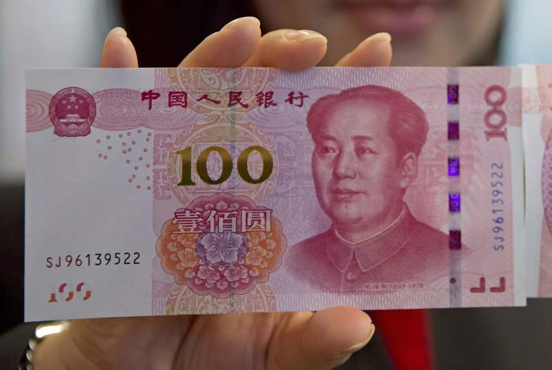 FILE - In this Nov. 12, 2015, file photo, staff member displays an 100-yuan RMB banknote at the Bank of China Tower in Hong Kong. Chinas central bank is trying to restrain the surging exchange rate of its currency, temporarily backtracking in efforts to make the tightly controlled yuan more flexible and market-oriented.  (AP Photo/Kin Cheung, File)