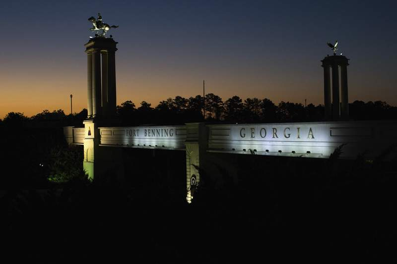 FILE - In this Oct. 16, 2015, file photo a bridge marks the entrance to the U.S. Army's Fort Benning as the sun rises in Columbus, Ga. The Senate on Thursday, July 23, 2020, joined the House in defying a veto threat from President Donald Trump to approve defense legislation that would remove the names of Confederate officers from American military bases such as Fort Bragg and Fort Benning. (AP Photo/Branden Camp, File)