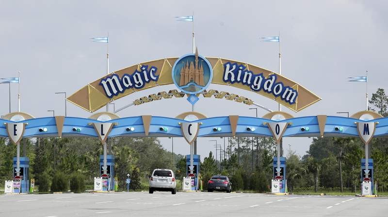 FILE - Park guests enter the Magic Kingdom during the reopening of Walt Disney World, Saturday, July 11, 2020, in Lake Buena Vista, Fla. Walt Disney Co. reported net income that plummeted dramatically in the third quarter, when it most of its theme parks remained closed and theatrical movie releases were postponed. Net income results were better than the loss analysts expected, however, but revenue missed expectations. (AP Photo/John Raoux)