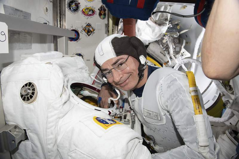 In this Aug. 17, 2021 photo made available by NASA, astronaut and Expedition 65 Flight Engineer Mark Vande Hei inspects a spacesuit in preparation for a spacewalk at the International Space Station. On Monday, Aug. 23, NASA announced it is delaying a spacewalk this week because of an undisclosed medical issue involving Vande Hei. (NASA via AP)