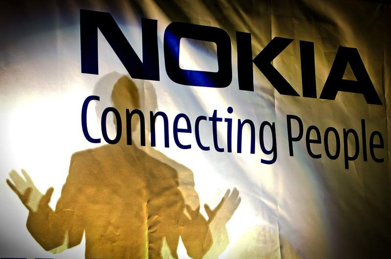 FILE -- In this Feb. 11, 2008 file picture, general manager of the Nokia factory in Romania, John Guerry, casts a shadow on a banner at the new Nokia factory in Jucu, central Romania, during the official opening of the first production line. Nokia says it has been tapped by NASA to build the first cellular communications network on the Moon. The Finnish technology giant said Monday, Oct. 19, 2020 its Nokia Bell Labs' division will build a 4G communications system to be deployed on a lunar lander to the Moon's surface in late 2022.  (AP Photo/Vadim Ghirda, File)