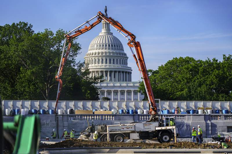 FILE - A concrete pump frames the Capitol Dome during renovations and repairs to Lower Senate Park on Capitol Hill in Washington, Tuesday, May 18, 2021. Plans to pump money into rebuilding the nations roads, bridges and other infrastructure could give companies that make machinery and materials a solid foundation for growth. (AP Photo/J. Scott Applewhite, file)