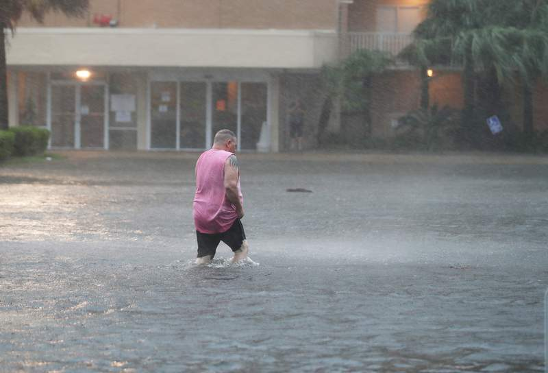 A man walks though a flooded parking lot as the outer bands of Hurricane Sally come ashore on Sept. 15 in Gulf Shores, Alabama.