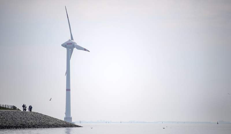 Cyclists ride along the dyke in Emden, Germany, Wednesday, June 3, 2020. The German government wants to increase offshore wind power capacity five-fold by 2040 as part of its plan to wean the country off fossil fuels. Cabinet on Wednesday agreed a bill that would set a goal of 40 Gigawatts of installed offshore wind power capacity in 20 years, from about 7.5 Gigawatts at present. It also raised the target for 2030 from 15 Gigawatts to 20. (Sina Schuldt/dpa via AP)