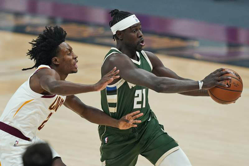 Milwaukee Bucks' Jrue Holiday (21) drives against Cleveland Cavaliers' Collin Sexton (2) in the first half of an NBA basketball game, Saturday, Feb. 6, 2021, in Cleveland. (AP Photo/Tony Dejak)