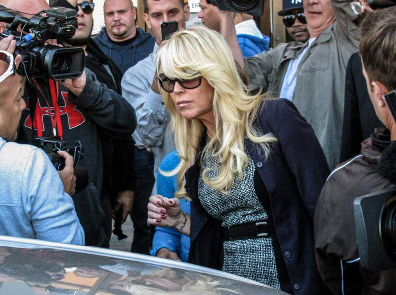 FILE - In this Sept. 24, 2013 file photo, Dina Lohan leaves court in Hempstead, N.Y., after pleading not guilty to drunken driving charges. Lohan pleaded guilty to drunken driving on Tuesday, Sept. 28, 2021, and is expected to be sentenced to 18 days in jail and five years probation for rear-ending another car on Long Island and leaving the scene. (AP Photo/Frank Eltman, File)
