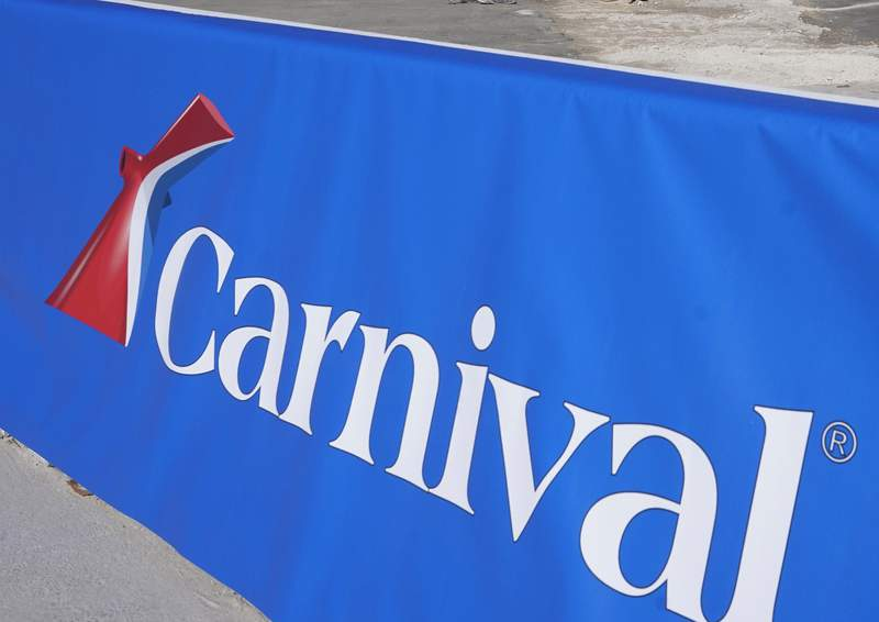 FILE - This Jan. 29, 2021 file photo shows a Carnival Cruise Line sign at PortMiami in Miami. The Belize Tourism Board says 27 people aboard a Carnival cruise tested positive for COVID-19 just before the ship made a stop in Belize City. The positive cases it reported Wednesday, Aug. 12, were among 26 crew members and one passenger on the Carnival Vista, which is carrying over 1,400 crew and nearly 3,000 passengers.  (AP Photo/Lynne Sladky, File)