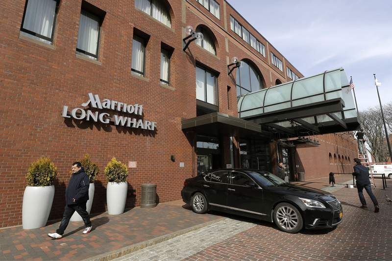 FILE - In this March 11, 2020 file photo, people walk outside the Marriott Long Wharf hotel in Boston. Marriott says it saw dramatic improvement in the third quarter as travel demand rebounded in China. (AP Photo/Steven Senne, File)