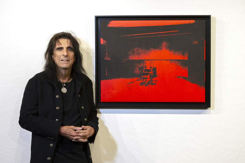 """In this photo provided by the Chris Loomis, singer Alice Cooper stands by his Andy Warhol red acrylic and silkscreen on canvas called """"Little Electric Chair"""" at the Larsen Gallery in Scottsdale, Ariz., on Wednesday, May 12, 2021. The Warhol canvas found years ago in the garage of rocker Alice Cooper could become the highest selling artwork ever in Arizona. The music legend, who has a home in metro Phoenix, announced Thursday, May 13, 2021, that he would auction off """"Little Electric Chair."""" The gallery estimates it could fetch anywhere from $2.5 million to $4.5 million. (Chris Loomis via AP)"""
