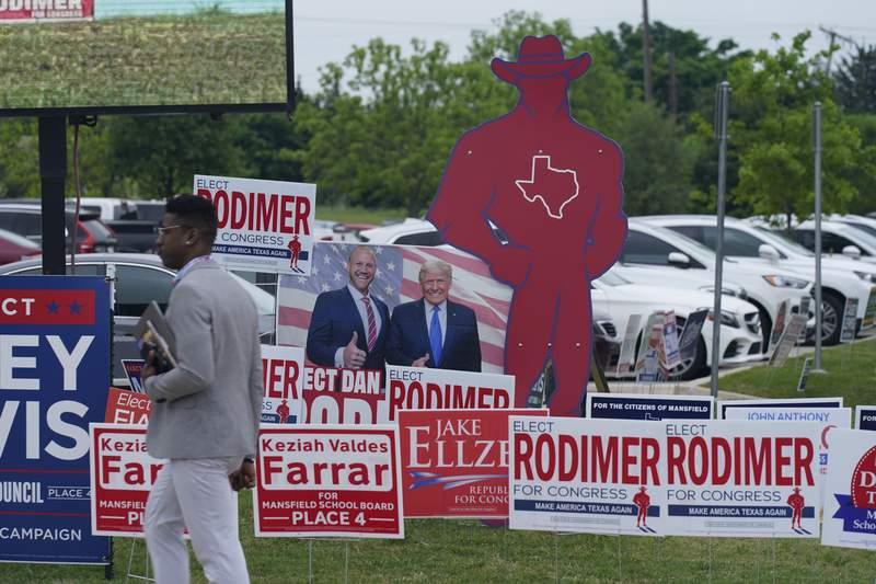 Sign supporting various candidates sit outside an early voting location Tuesday, April 27, 2021, in Mansfield, Texas. (AP Photo/LM Otero)