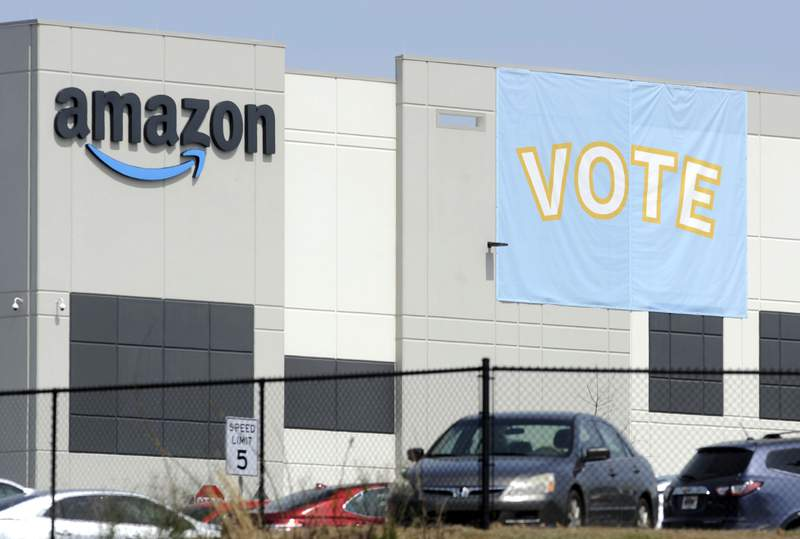 FILE - In this March 30, 2021 file photo, a banner encouraging workers to vote in labor balloting is shown at an Amazon warehouse in Bessemer, Ala. The union that tried, and failed, to organize Amazon warehouse workers in Bessemer, says it may get a do-over. The Retail, Wholesale and Department Store Union on Monday, Aug. 2 said that a hearing officer for the National Labor Relations Board has recommended that the vote by workers in April to overwhelmingly reject the union be set aside and that another vote be held in its place. (AP Photo/Jay Reeves, File)