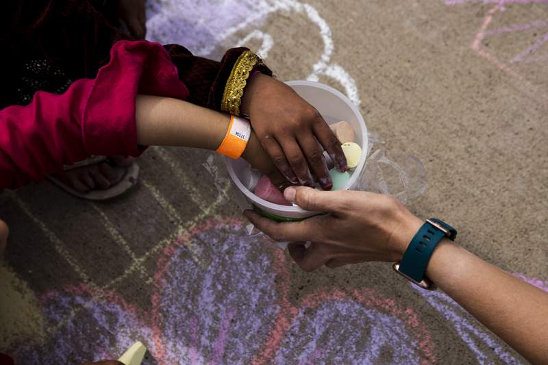 In this Aug. 31 , 2021, photo provided by the U.S. Army, Afghan children take a piece of chalk at a children's activity event held by non-governmental charities at Fort McCoy in Wisconsin. U.S. officials are looking into reports that in the frantic evacuation of desperate Afghans from Kabul, older men were admitted together with young girls they claimed as brides or otherwise sexually abused. One internal document seen by The Associated Press says the State Department has sought urgent guidance from other agencies after purported child brides were brought to Fort McCoy. (Spc. Rhianna Ballenger/U.S. Army via AP)
