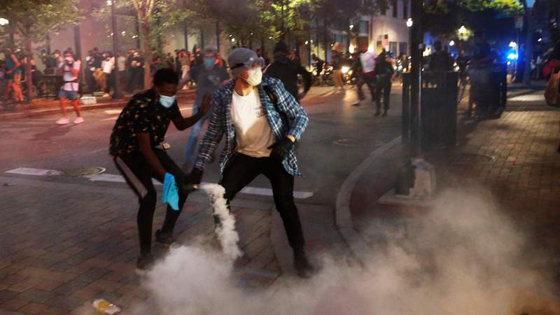 A protester tosses a smoke bomb towards police during a third night of unrest Sunday May 31, 2020, in Richmond, Va. Gov. Ralph Northam issued a curfew for this evening. The smoke bomb was ignited by a protester. (AP Photo/Steve Helber)