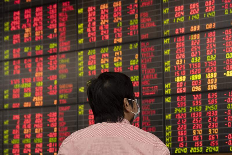 A Thai investor checks an electronic board showing stock prices at Asia Plus Securities, a private stock trading floor, in Bangkok, Thailand, Friday, March 13, 2020. Shares plunged in Asia on Friday, with benchmarks in Japan, Thailand and India sinking as much as 10% after Wall Street suffered its biggest drop since the Black Monday crash of 1987. (AP Photo/Sakchai Lalit)