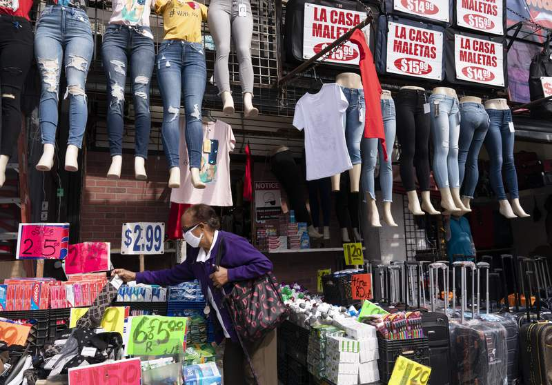 FILE - In this Sept. 25, 2020 file photo, a woman shops at a clothing store in New York. The U.S. economy grew at a sizzling 33.1% annual rate in the July-September quarter  by far the largest quarterly gain on record  rebounding from an epic plunge in the spring, when the eruption of the coronavirus closed businesses and threw tens of millions out of work.  (AP Photo/Mark Lennihan, File)