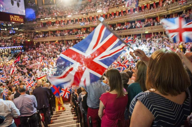 FILE  - In this Sept. 13, 2014 file photo, members of the audience react during the Last Night of the Proms at the Royal Albert Hall, London. The BBC has ditched the lyrics of Rule Britannia! for its traditional summer-ending concert amid a controversy over the songs celebration of the British Empire at a time when critics are re-evaluating the nations colonial past. Britains publicly funded broadcaster said the final night of its Proms concert series would feature instrumental versions of Rule Britannia! and Land of Hope and Glory, instead of traditional singalongs.  (Guy Bell/PA via AP, File)