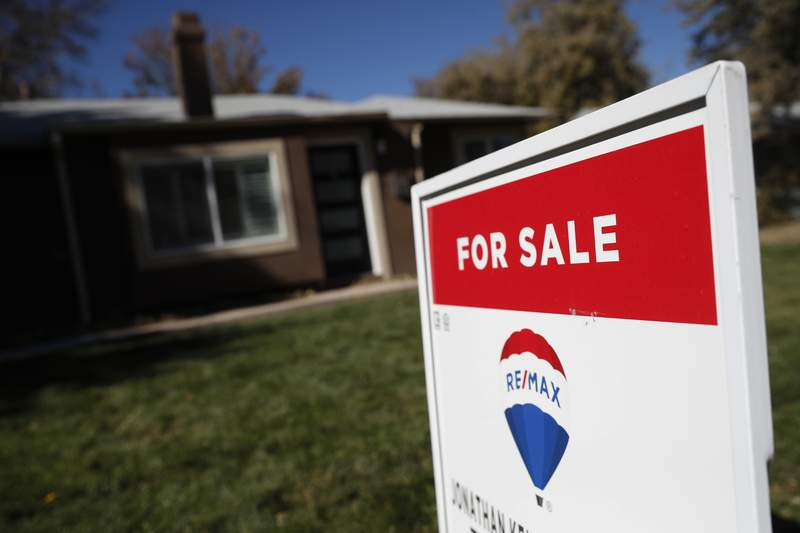 FILE - In this Oct. 22, 2019 file photo, a sign stands outside a home for sale in southeast Denver. U.S. long-term mortgage rates were flat this week, staying near record lows as the economy remains burdened by the coronavirus pandemic. Mortgage buyer Freddie Mac reports that the average rate on the benchmark 30-year fixed-rate home loan remained at last weeks 2.73%. The average rate on 15-year fixed-rate loans ticked up to 2.21% from 2.20%. The government reported Thursday, Feb.  4, 2021 that the number of Americans seeking unemployment benefits fell to 779,000 last week, a still-historically high total showing that a sizable number of people keep losing jobs to the coronavirus pandemic. (AP Photo/David Zalubowski, File)