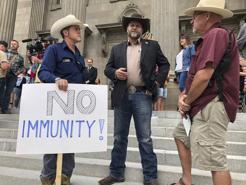 FILE - In this Aug. 24, 2020, file photo Ammon Bundy, center, who led the Malheur National Wildlife Refuge occupation, stands on the Idaho Statehouse steps in Boise, Idaho. A bill to make illegal demonstrating at a person's residence headed to the full House on Friday, Feb. 19, 2021, after a series of demonstrations at the homes of officials and police officers spurred by frustration with restrictions on gatherings or mask-wearing mandates to slow infections and deaths because of the coronavirus pandemic. Many of those testifying against the bill used terms common among anti-government activist Bundy and his People's Rights network, contending in general the people were having their rights taken away. (AP Photo/Keith Ridler, File)
