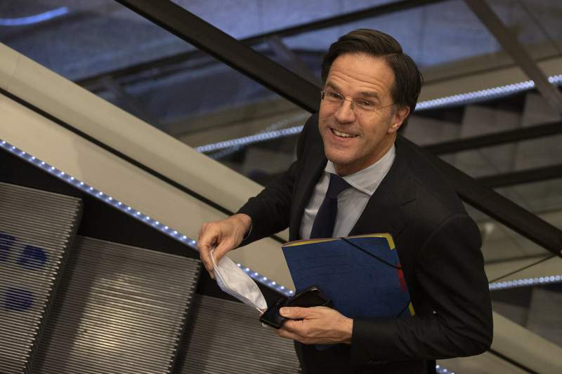 FILE - In this file photo dated Friday, April 2, 2021, caretaker Dutch Prime Minister Mark Rutte leaves after surviving a no-confidence motion in parliament in The Hague, Netherlands.  The Dutch government on Tuesday April 13, 2021, presented a roadmap for relaxing coronavirus lockdown measures, but caretaker Prime Minister Mark Rutte said it is still too early to relax the countrys months-long lockdown.  (AP Photo/Peter Dejong, FILE)
