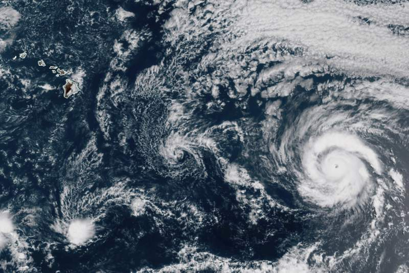 This GOES-17 taken at 3:30 p.m. EDT, Thursday, July 23, 2020, shows Hurricane Douglas, right, churning in the Pacific Ocean heading towards Hawaii, left. The storm is currently a Category 3 hurricane but is expected to weaken before it arrives in the state this weekend. (NOAA via AP)