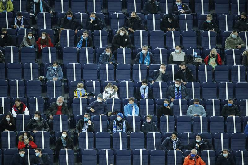 Spectators wearing face masks to protect against coronavirus watch the Champions League group F soccer match between Zenit St.Petersburg and Borussia Dortmund at the Saint Petersburg stadium in St. Petersburg, Russia, Tuesday, Dec. 8, 2020. (AP Photo/Dmitri Lovetsky)