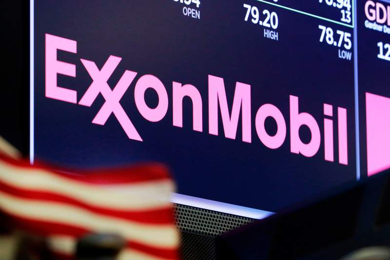 FILE - In this April 23, 2018, file photo, the logo for ExxonMobil appears above a trading post on the floor of the New York Stock Exchange.   Exxon Mobil is facing a major challenge from a group of investors in one of the biggest fights a corporate boardroom has faced over its stance on climate change, an issue of rising urgency among many shareholders. The investor group is pushing to replace four of the oil giants board members with executives who they say are better suited to make money and to lead the company through a transition to cleaner energy. (AP Photo/Richard Drew, File)