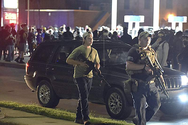 Kyle Rittenhouse, left, with backwards cap, walks along Sheridan Road in Kenosha, Wis., Tuesday, Aug. 25, 2020, with another armed civilian. (Adam Rogan/The Journal Times via AP)